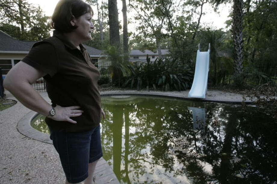 POOL DEBRIS:Rita Boyer looks at her pool on Sept. 23, at  her residence in Fawnlake Drive in West Memorial, where a tree blown over by Hurricane Ike landed inside the pool. Boyer said she added 50 goldfish as a way of mosquito control on her pool. Photo: Julio Cortez, Chronicle