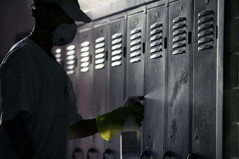Wilmer Martinez cleans a set of lockers at Central Middle School in Galveston on Friday. Photo: Eric Kayne, Chronicle