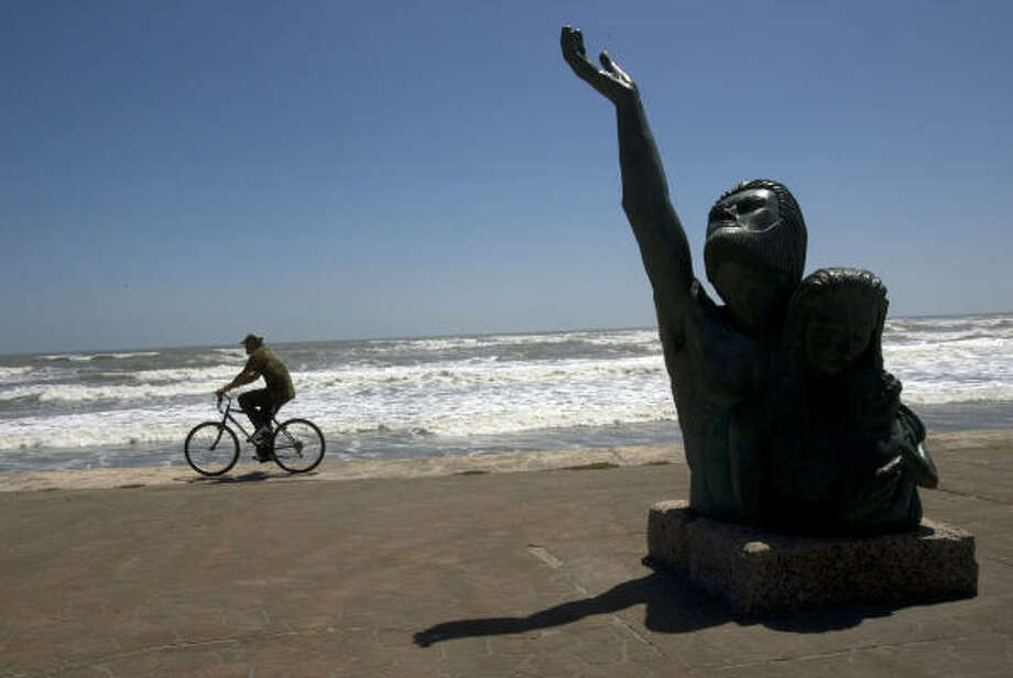 Galveston resident Larry Oliver rides his bike on the seawall past the memorial for the great hurricane of 1900 before Hurricane Ike's arrival in Galveston on Thursday, Sept. 11, 2008. Photo: Johnny Hanson, Houston Chronicle