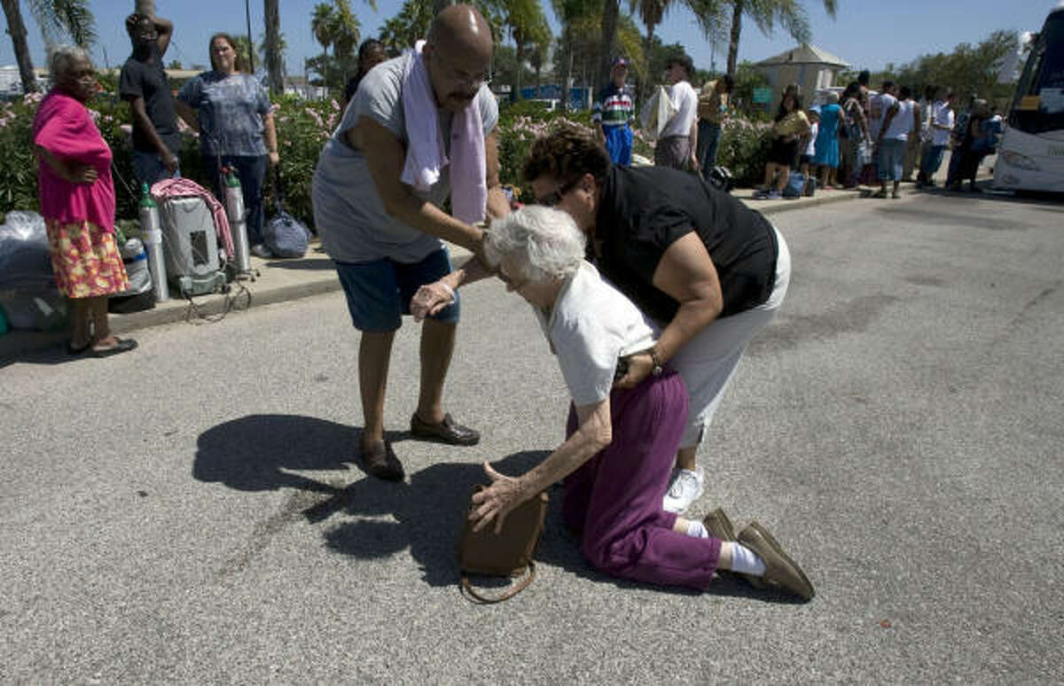 Galveston resident Elizabeth Schadt is helped up after falling as hundreds waited for buses that would take them to a shelter in Austin at the Island Community Center in preparation of Hurricane Ike.