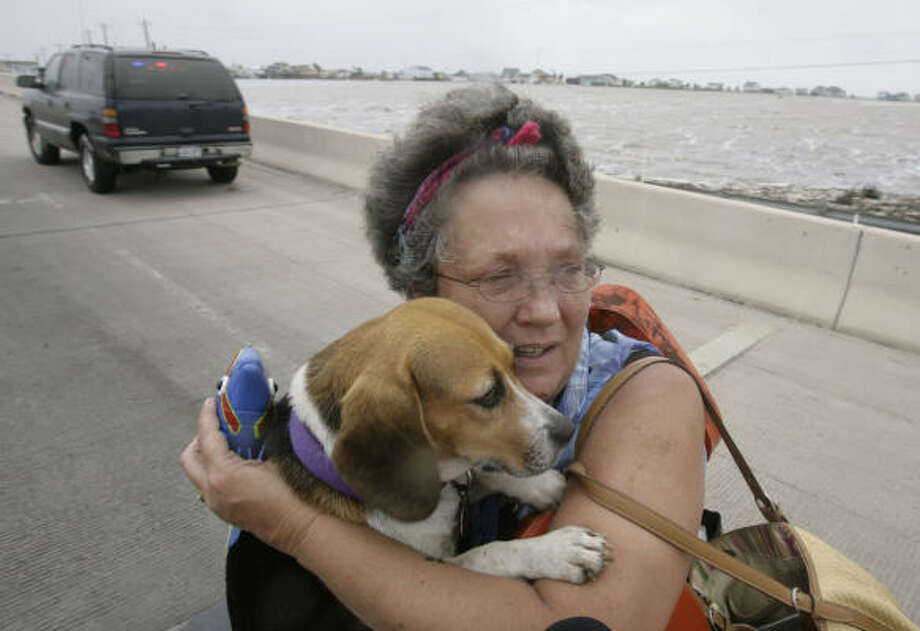 Dondi Fields, 50, holds on to her dog Sandy Beach after she, the dog and her husband, David Fields, were rescued by officials as they tried to evacuate from their Surfside Beach home with Hurricane Ike approaching. Photo: Julio Cortez, Chronicle