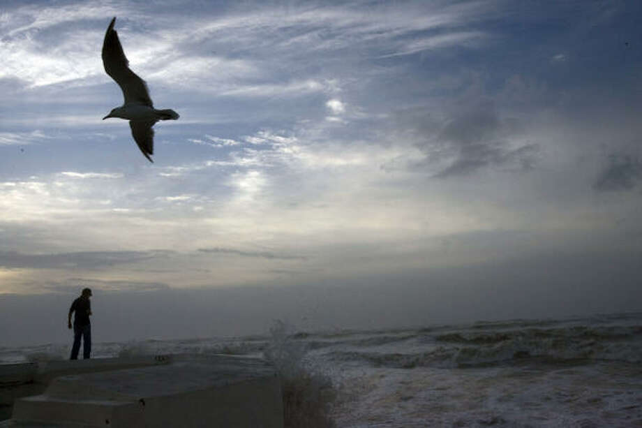 As the clouds of Hurricane Ike began to approach, Daniel Gallegos, 26, of Galveston, watches waves braking over the seawall in Galveston as Hurricane Ike approached Friday, Sept. 12, 2008. Photo: Johnny Hanson, Houston Chronicle