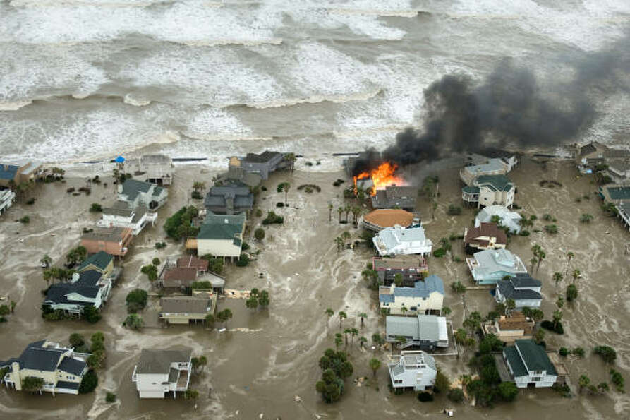 A house is totally engulfed in flames as floodwaters and crashing waves inundated beach homes on Gal