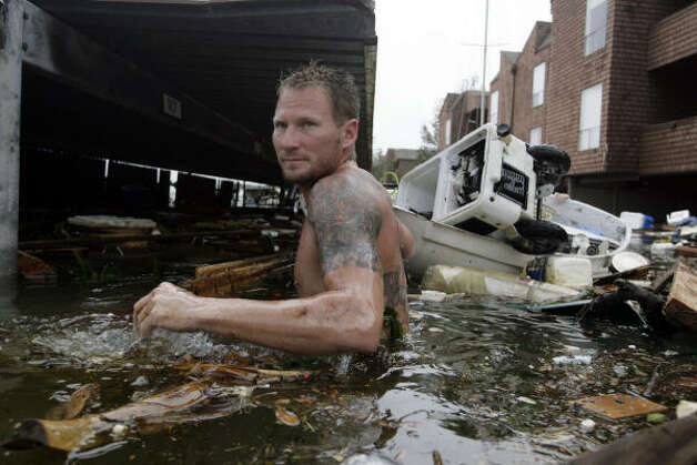 B.J. Gabbert helps friends David Richey and Wesley Lichenstein recover Richey's outboard motor from his sailboat at an apartment complex in El Lago after Hurricane Ike. Photo: Eric Kayne, Chronicle