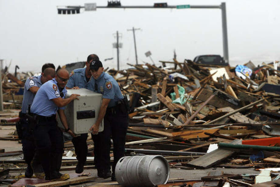 Galveston police officers remove a safe from the rubble of the Hooters restaurant on Seawall Boulevard after the restaurant was wrecked by Hurricane Ike. Photo: Johnny Hanson, Houston Chronicle