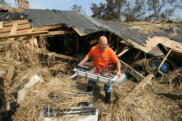 David Smith salvages his tools from his Bridge City home. Smith's childhood home was destroyed by the storm surge caused by Hurricane Ike. Photo: Billy Smith II, Chronicle