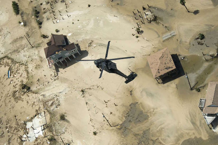 A military helicopter flies over houses damaged by Hurricane Ike in Crystal Beach. Photo: Smiley N. Pool, Houston Chronicle