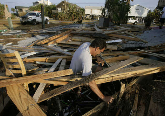 John Theriot looks through what Hurricane Ike left under his destroyed home after Jamaica Beach residents were allowed back on the island to assess damages. Photo: Julio Cortez, Chronicle
