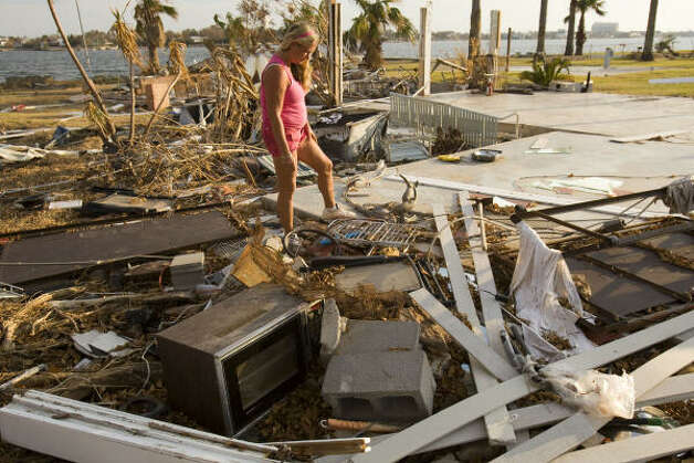 Brenda Roby walks through a mass of debris where her home once stood in the aftermath of Hurricane Ike in Galveston. Photo: Brett Coomer, Chronicle