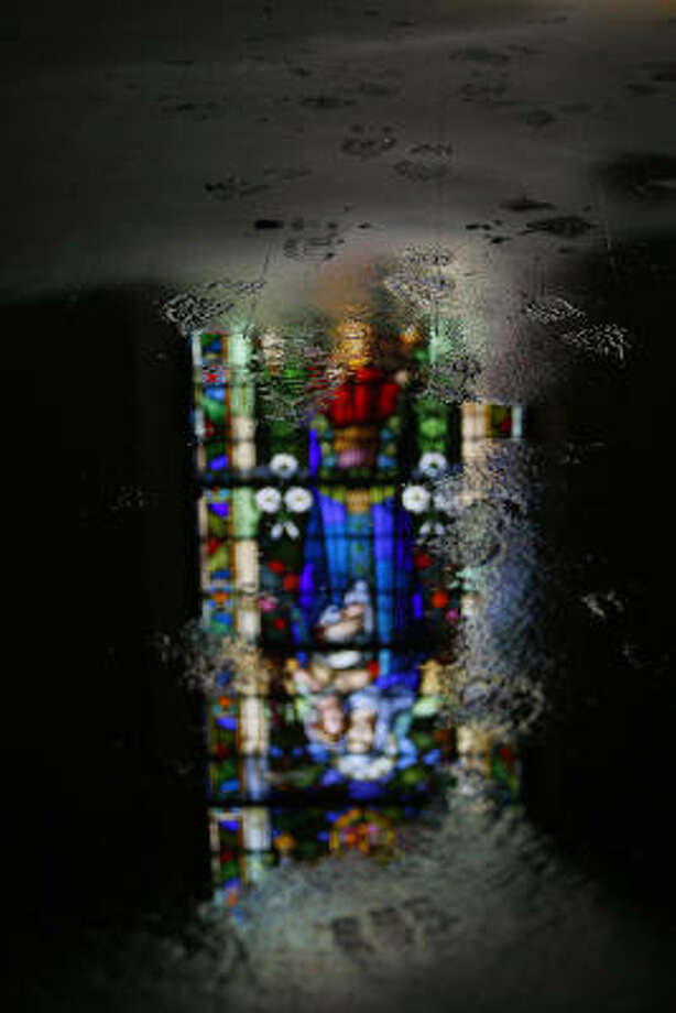 Footprints show the movement of worker crews cleaning up the historical Trinity Episcopal Church in Galveston that survived Hurricane Ike with flooding, down trees, and a broken stained-glass window behind the altar. Photo: Mayra Beltran, Houston Chronicle