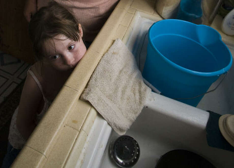 Ginger Spahni's daughter Kloey Spahni rests her head by the kitchen sink Tuesday, where her mom washes dishes with water carried in a plastic pail. Photo: Steve Ueckert, Houston Chronicle