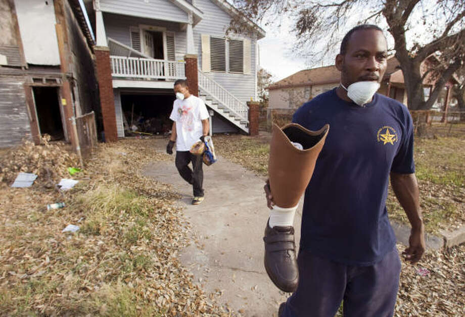 John Levine, right, carries his father's prosthetic leg as he and his nephew Anthony Levine begin cleaning up in the aftermath of Hurricane Ike. Photo: Brett Coomer, Chronicle
