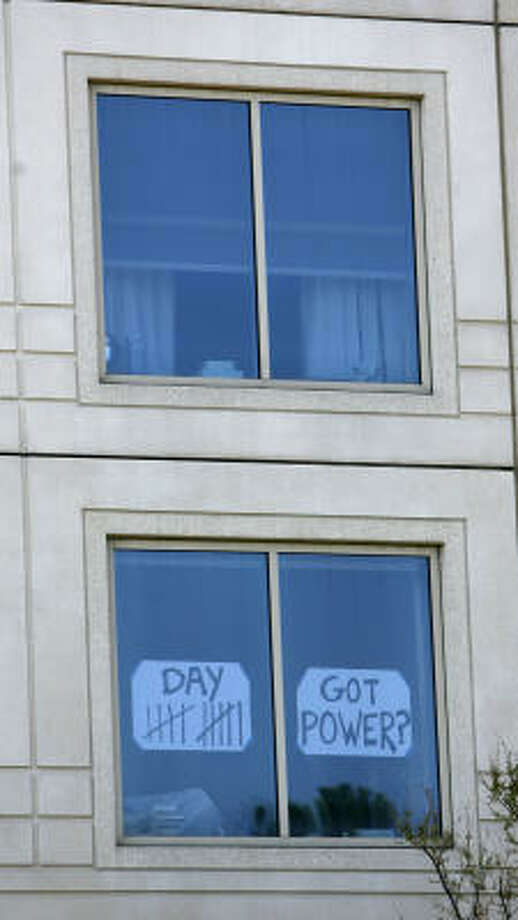 A sign in the window of a high-rise on Allen Parkway, marks the number of days that the power has been down in the building. Photo: Karen Warren, Chronicle