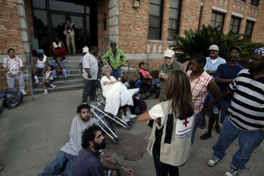 Vicki Worrall, a worker with Red Cross, talks to evacuees at an evacuation shelter where 500 people are expected to arrive and use their services by Sunday in Galveston. Photo: Eric Kayne, Chronicle