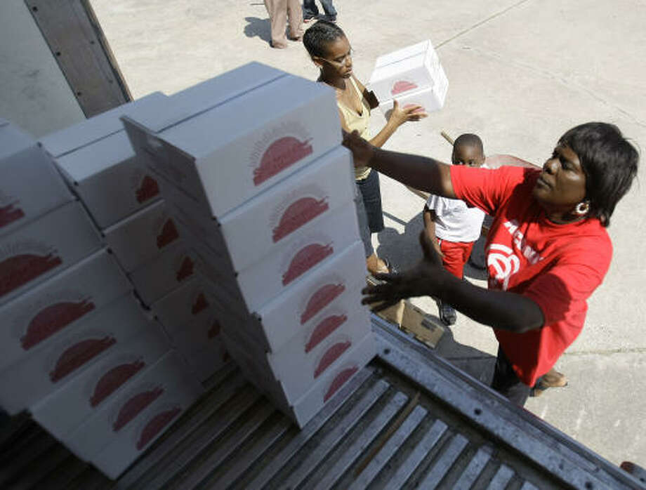 Georgia Menson, a volunteer with the Association of Community Advocating for Reform Now, grabs boxes from the back of an 18-wheeler as she and other volunteers hand out boxes of food. Photo: Karen Warren, Chronicle