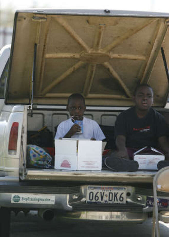 Cory Johnson, 5, and his brother, Edward, 8, sit in the back of their pickup as they eat their lunch, which was handed out by ACORN volunteers. Photo: Karen Warren, Chronicle