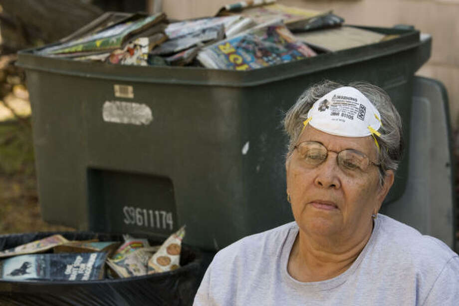 Delores Hernandez sits down in the shade after spending most of the day cleaning up her flood-damaged home in Galveston. Photo: Brett Coomer, Chronicle