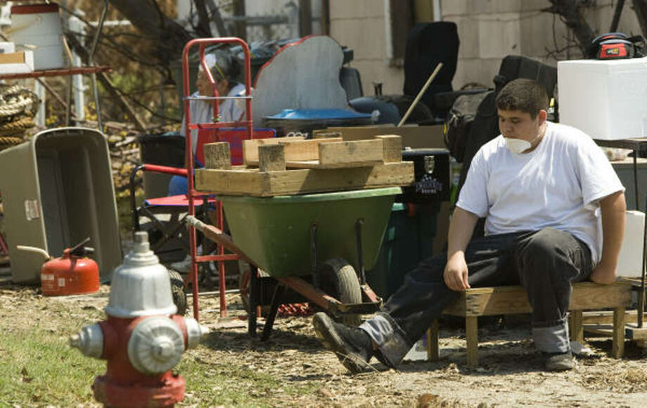 John Hernandez takes a break from clearing flood damage from his grandmother's Galveston home. Photo: Brett Coomer, Chronicle