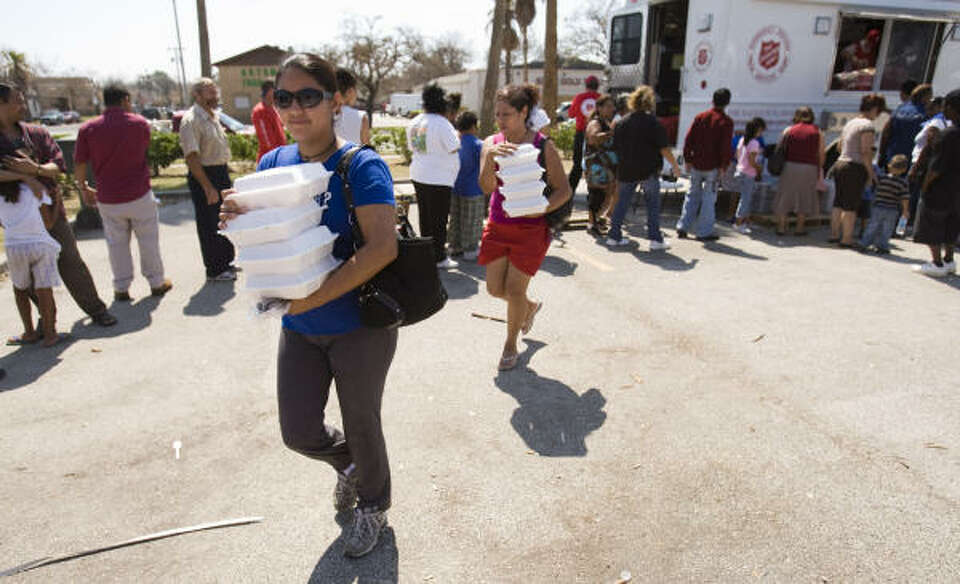 Maria Ramierz, left, and Tina Zarate carry containers of food delivered by the Salvation Army to the