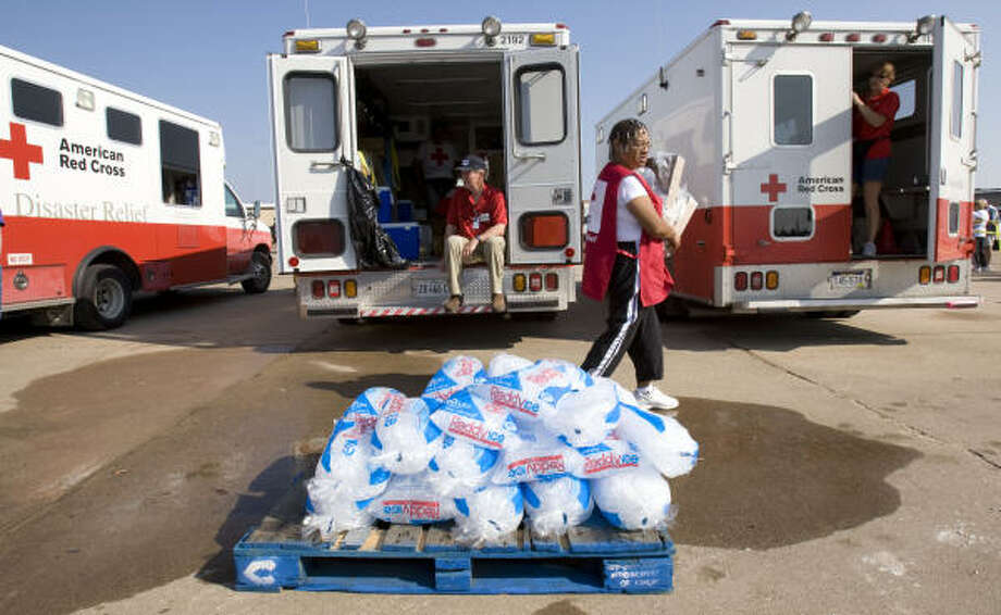 Red Cross volunteer Mary Jamison, of Hopewell, Va., walks past a pallet of ice and a line of Red Cross disaster relief vehicles being prepared to take meals to the people of Galveston. Photo: Brett Coomer, Chronicle