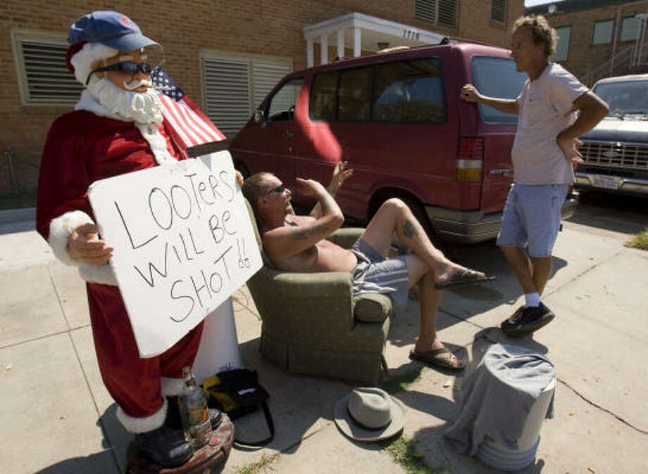 Michael Sims, seated, talks to Steven Stidhem outside Sims' apartment in Galveston. Photo: Brett Coomer, Chronicle
