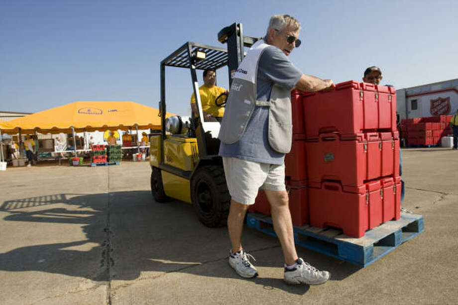Ray Yelle, of Alfred, N.Y., helps guide a forklift full of food to a staging area as he works with other volunteers to deliver food to the people returning to Galveston. Photo: Brett Coomer, Chronicle