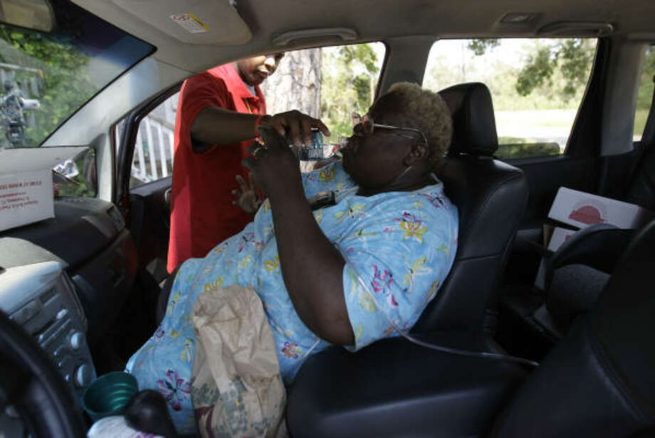 Edna Barlow receives medication from her grandson, Eddie Patt, 21, as she sits in her car in front of her house. Photo: Karen Warren, Chronicle