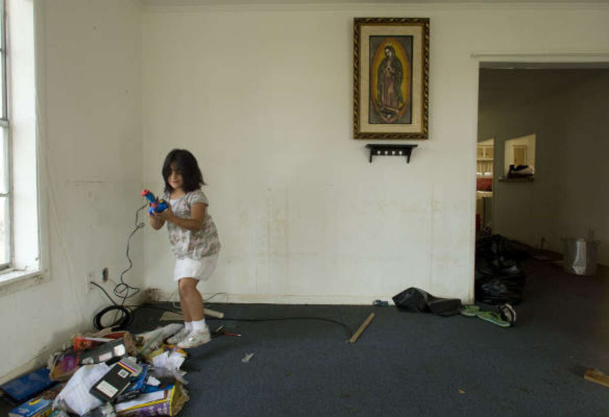 Maria Balderas, 6, salvages a damaged toy as she helps clean her family's home in Galveston Sept. 24.