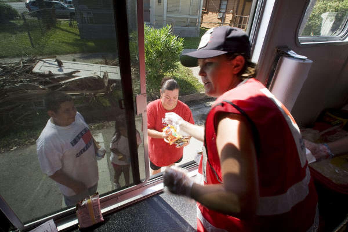 Red Cross volunteer Brinda Peterson hands food to Guadalupe Gutierrez and her children, Valeria, 6, and son, Juan, 11, in Galveston on Sept. 24.