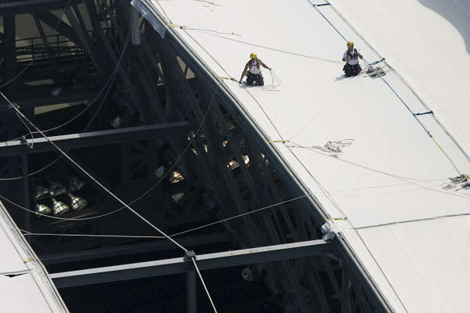Workers make repairs to the roof of Reliant Stadium in Houston. Photo: Smiley N. Pool, Chronicle