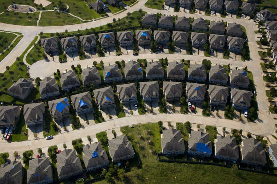 Blue tarps dot damaged roofs of a subdivision on the far west side. Photo: Smiley N. Pool, Chronicle