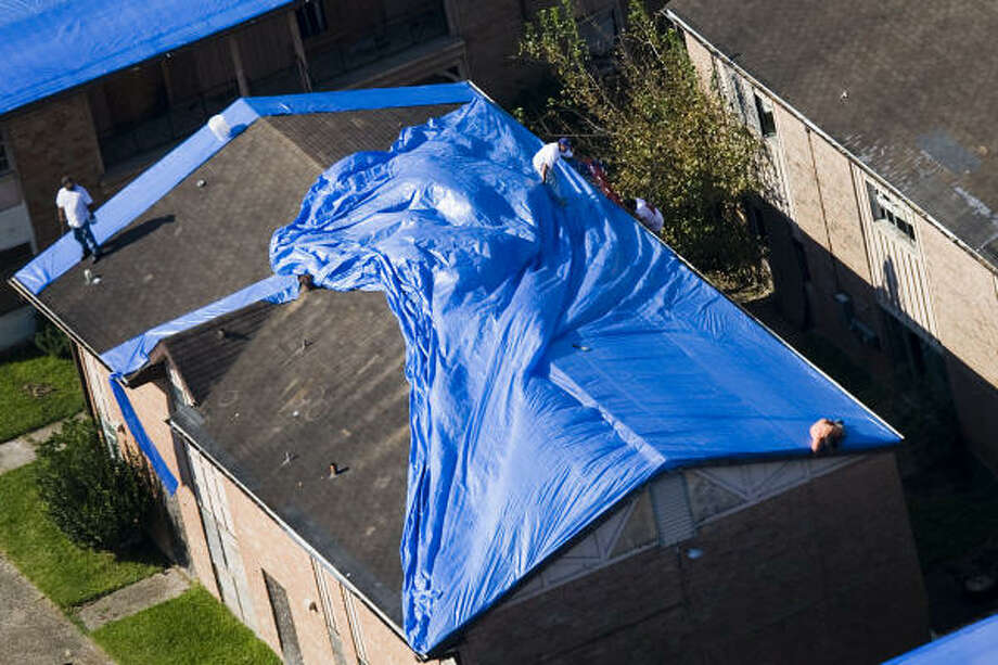 Men spread a blue tarp on a roof top near Hobby Airport in Houston. Photo: Smiley N. Pool, Chronicle