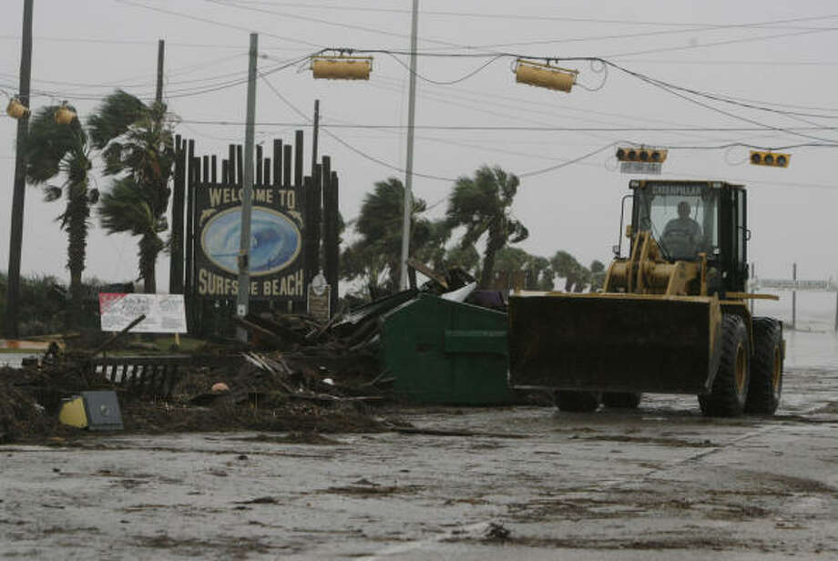 Crews clean up debris Sept. 13 left by Hurricane Ike in Surfside Beach. Photo: Julio Cortez, Chronicle