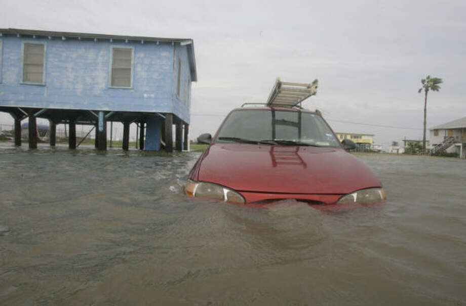 This vehicle was seen a day earlier as its owner tried to drive out of Surfside Beach through floodwaters. It is seen abandoned Sept. 13 a few blocks from the owner's residence. Photo: Julio Cortez, Chronicle