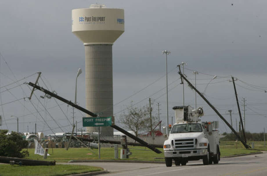 An electric company service truck drives Sept. 14 near downed power lines and posts in Freeport. Photo: Julio Cortez, Chronicle