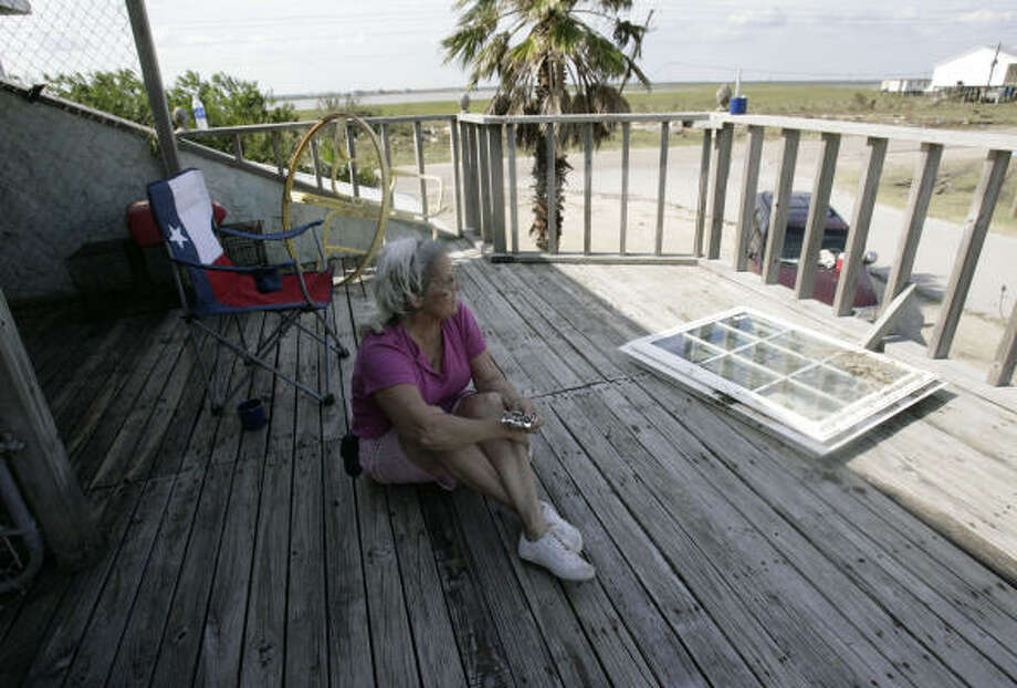 Marcy Orr relaxes on the porch of her second-floor apartment Sept. 15 as she and her husband, Phillip Orr, were allowed to go through their Surfside Beach home to assess damages from Hurricane Ike. Photo: Julio Cortez, Chronicle