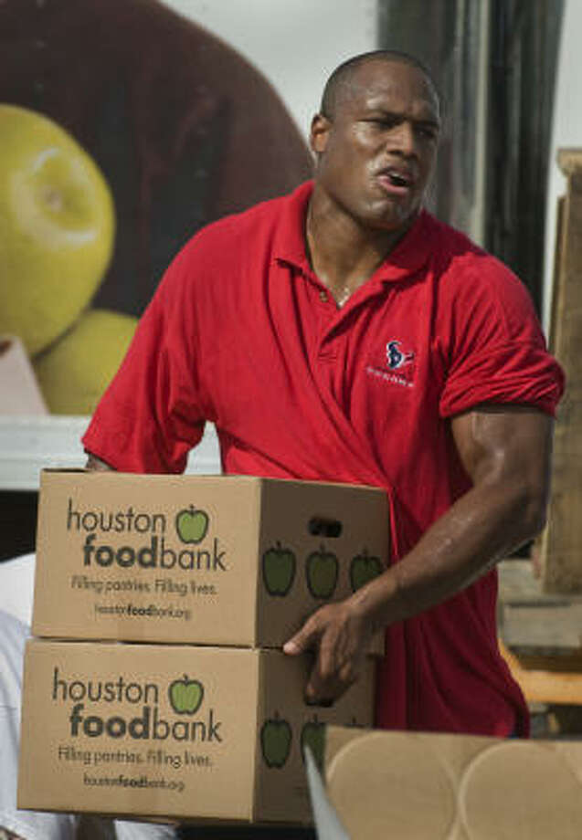Members of the Houston Texans football team, including offensive lineman Anthony Weaver, volunteer Tuesday morning at the Houston Food Bank helping those in need following Hurricane Ike. Photo: Steve Ueckert, Chronicle