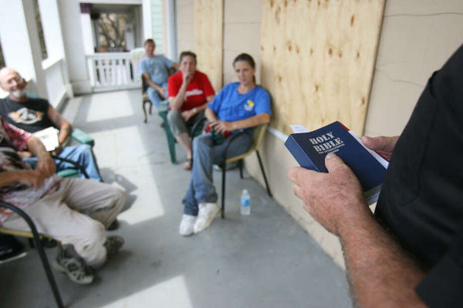Galveston Residents listen to Rev. John Bostock, from Christian Unitarian Church, as he is about to read a passage from the Holy Bible during an informal service on Saturday, Sept. 20. Photo: Mayra Beltran, Houston Chronicle