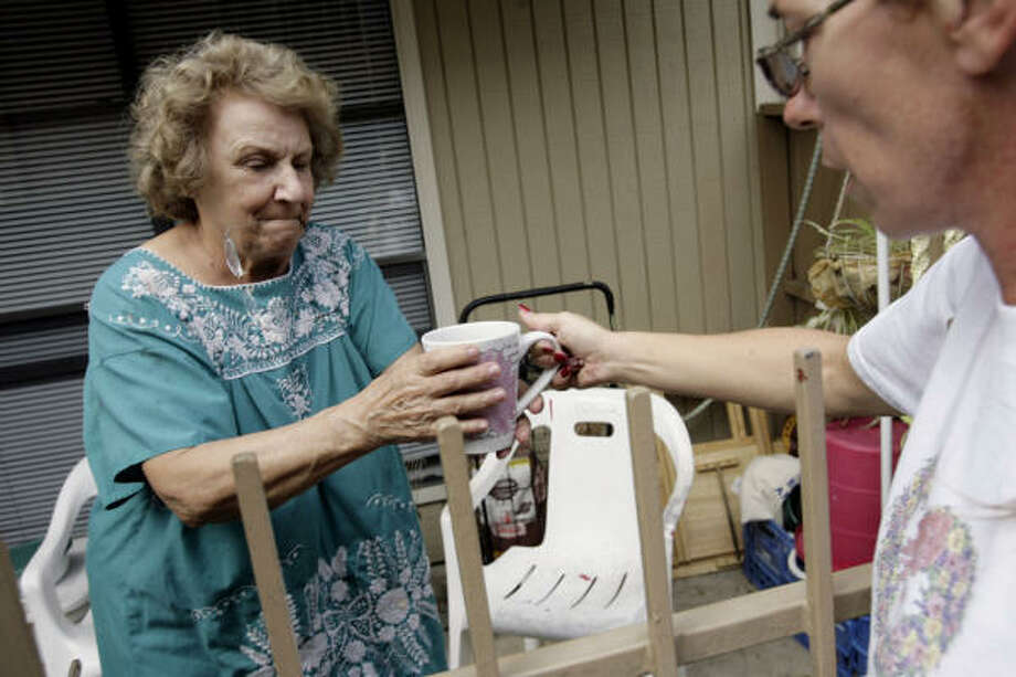Elaine Anzaldua, right, senior marketing associate at the Braesridge Senior Complex hands hot coffee and ice to Janet Laury at the Braesridge Senior Complex Sept. 17. Many seniors have been stranded at the Braesridge Senior Complex. Neighbors have come together to help each other out. Photo: Eric Kayne, Chronicle