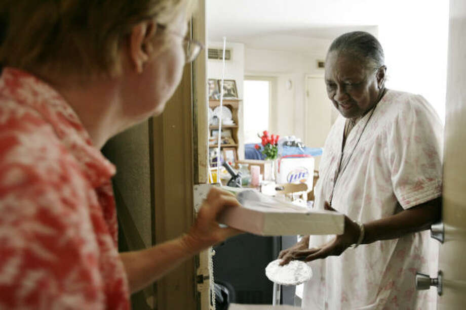 Terry Kreid delivers a meal to her neighbor Artelia Ross while navigating through darkened hallways at Braesridge Senior Complex, Sept. 17, in Houston. Meals were cooked by another neighbor under a carport. Photo: Eric Kayne, Chronicle