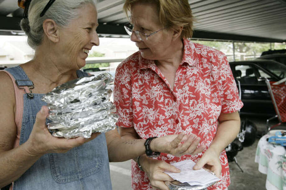 Sheryl Knotts, left, and Terry Kreid get ready to deliver meals to their neighbors while navigating through darkened hallways at Braesridge Senior Complex, Sept. 17 in Houston. Meals were cooked by another neighbor, Sylvia June, under a carport. Photo: Eric Kayne, Chronicle