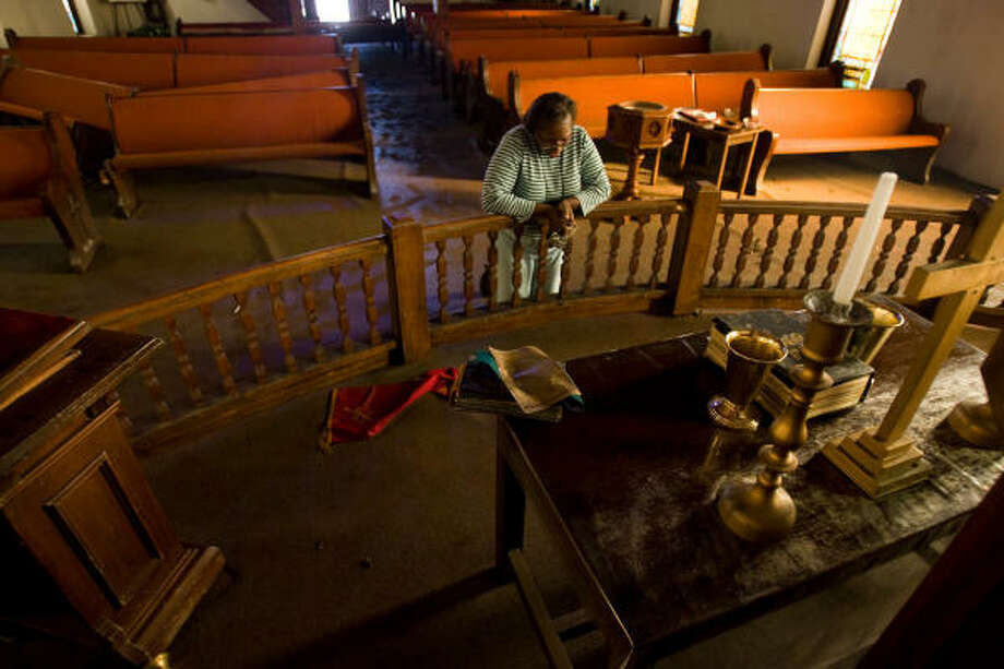 Salatheia Bryant-Honors, co-pastor of Reedy Chapel A.M.E., prays on Wednesday after taking her first look at the historic church after Hurricane Ike flooded Galveston. Photo: Nick De La Torre, HOUSTON CHRONICLE