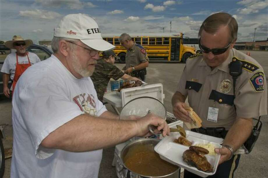 Volunteer Doug Kennard serves baked beans and barbequed chicken, Tuesday, to Spring Branch ISD Chief Chuck Brawner (right) in the Tully Stadium parking lot on Dairy Ashford. Gordon Knight (far left) volunteered his smoker and time to prepare the chicken which was donated and cooked by wood that also was donated. Photo: Steve Ueckert, Chronicle