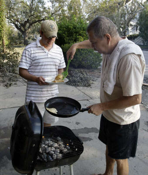 Pete Rodriguez, right, serves breakfast cooked on the grill to John Cangelosi in Galveston on Wednes