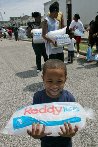Kristofer Sutton, bottom, 6, smiles after receiving ice from volunteers at a distribution center at