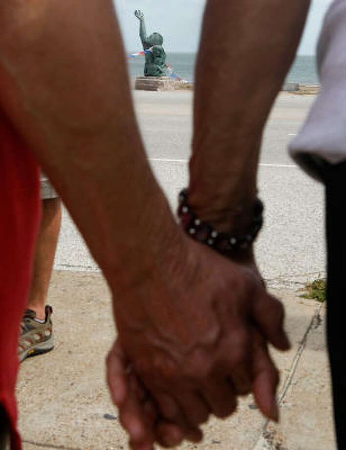 People in Galveston hold hands during a prayer vigil in front of the a sculpture that commemorates the 1900 Hurricane that killed over 6000 people. Photo: Mark Wilson, Getty Images
