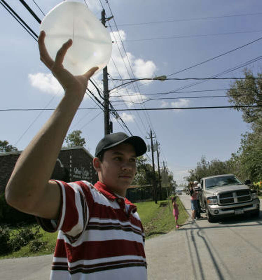 Matthew Bosquez holds up a bottle of water as he hands out water and food to people affected by Hurricane Ike near his church Wednesday, Sept. 17, in Seabrook, Texas. Photo: Frank Franklin II, AP