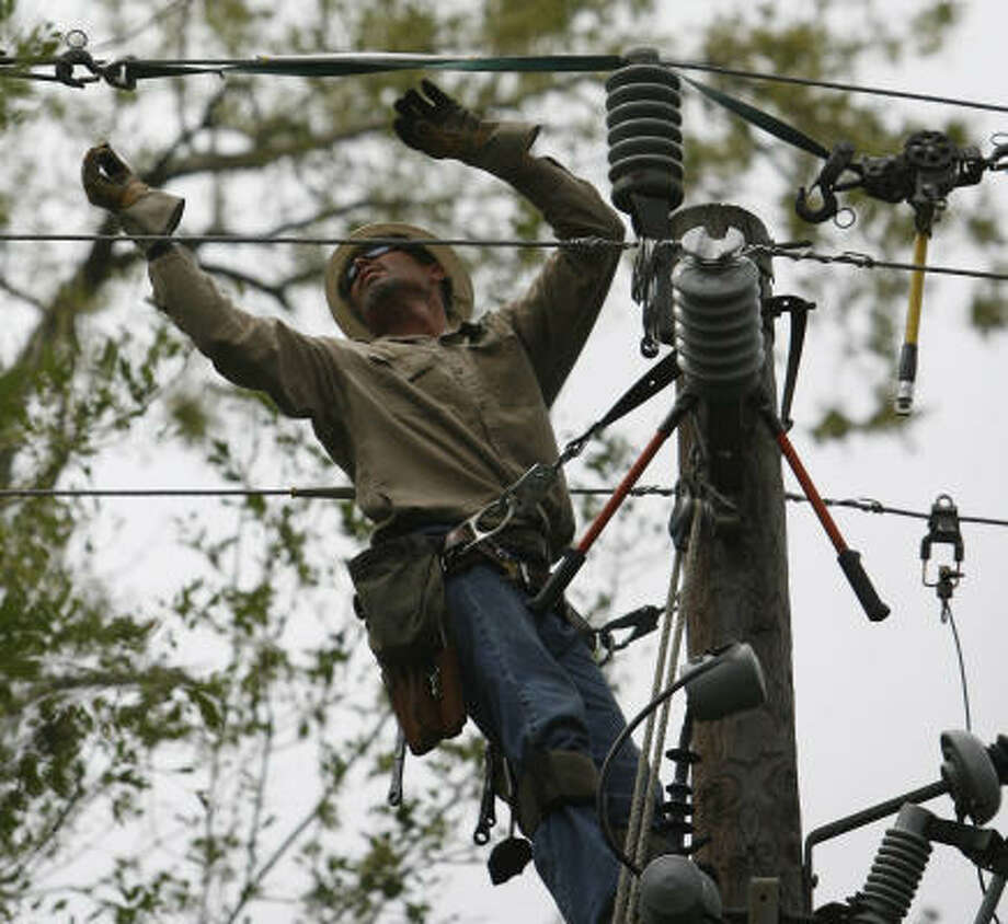 Helping to restore power to residents in the area, Centerpoint Energy linemen Kevin Allen works on power line in the back yard of Mount Belvieu resident near Baytown on Tuesday, Sept. 16. Photo: Billy Smith II, CHRONICLE