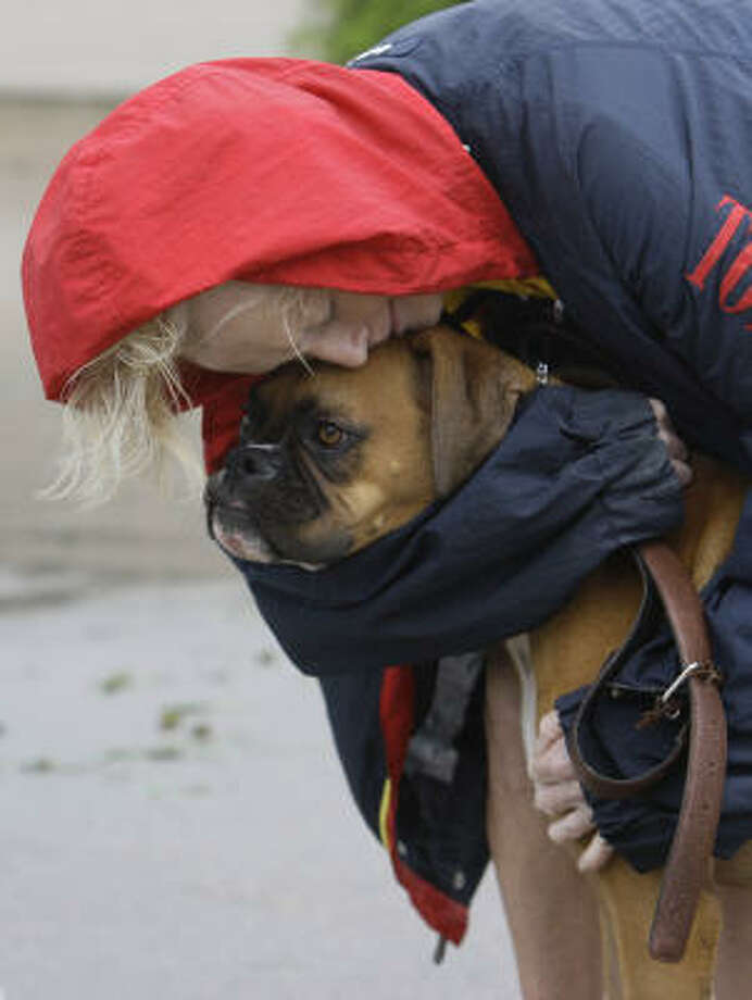 Frederika Kotin hugs her dog, Belle, on Saturday, Sept. 13. Hers was one of six town homes in a row that burned on Beaudelaire Circle in Galveston. She escaped with the clothes on her back, one shoe and her dog. Photo: Melissa Phillip, Chronicle