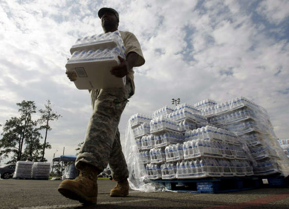 National Guardsman Konrad Herring hands out water to residents at a distribution center in Orange on Monday, Sept. 15. Photo: Eric Gay, AP